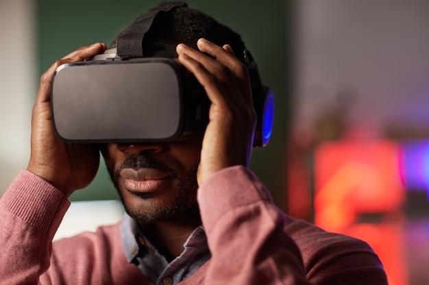 Close de um jovem africano de óculos durante um jogo de realidade virtual