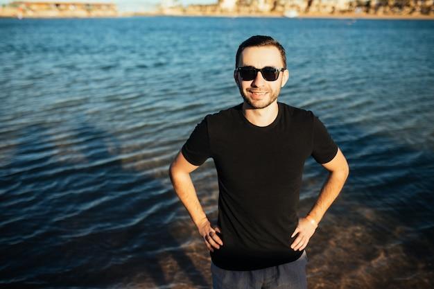 Close de um jovem atraente de óculos escuros em uma camiseta preta em pé na praia do mar