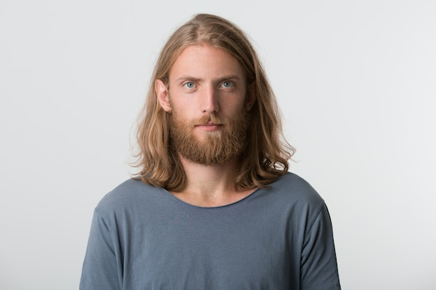 Close de um jovem atraente sério com barba e cabelo comprido loiro usa uma camiseta cinza parece pensativo e atencioso isolado sobre uma parede branca