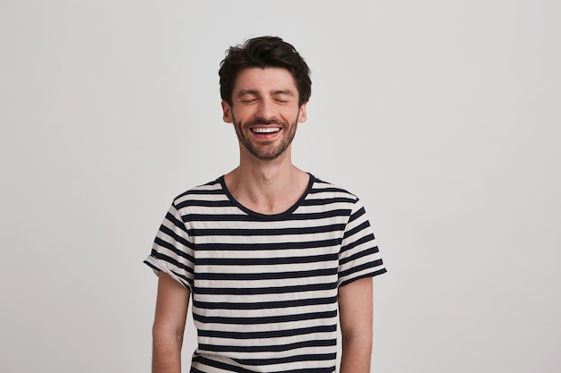 Close de um jovem atraente sorridente com cerdas usa uma camiseta listrada, mantém os olhos fechados e se sente animado em pé sobre uma parede branca
