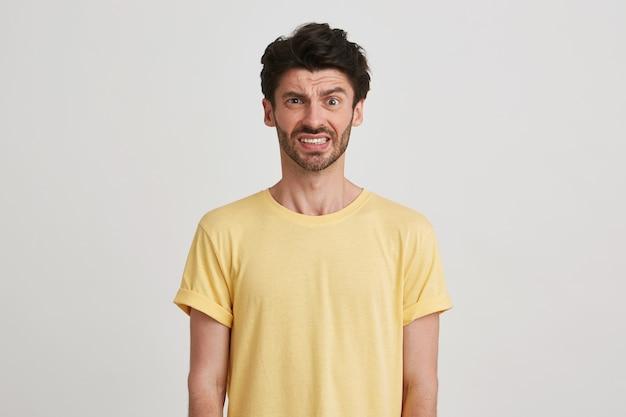 Close de um jovem barbudo descontente e infeliz vestindo uma camiseta amarela parece desapontado e franzindo a testa com o rosto isolado no branco
