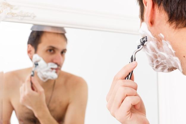 Close de um jovem bonito fazendo a barba no banheiro