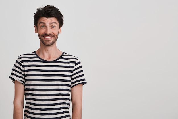 Close de um jovem bonito feliz com cerdas e vestindo uma camiseta listrada se sente surpreso e parece animado em pé sobre uma parede branca