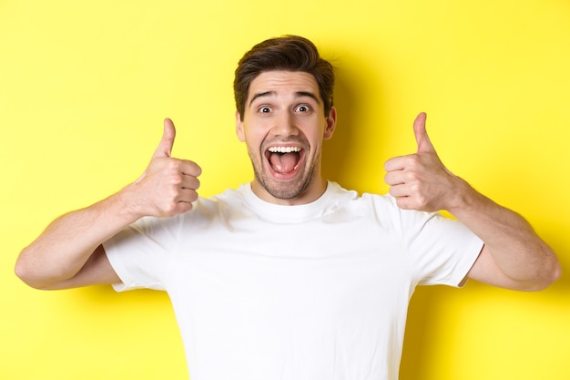 Close de um jovem bonito mostrando os polegares, aprovo e concordo, sorrindo satisfeito, em pé sobre um fundo amarelo