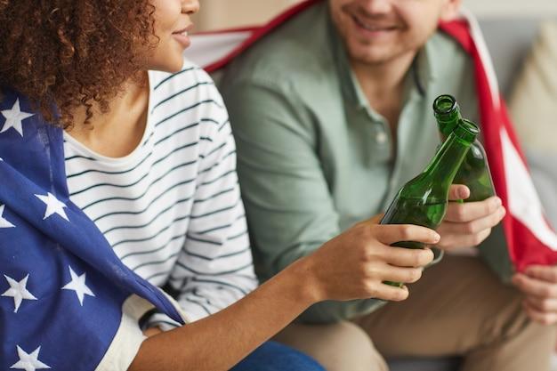 Close de um jovem casal mestiço batendo em garrafas de cerveja enquanto usa a bandeira americana