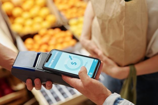 Close de um jovem casal pagando por produtos frescos com smartphone no mercado de alimentos orgânicos