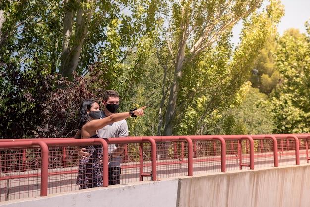 Close de um jovem casal usando máscaras faciais - conceito de novo normal
