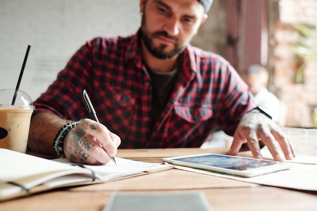 Close de um jovem concentrado sentado à mesa e elaborando uma lista de lugares para visitar