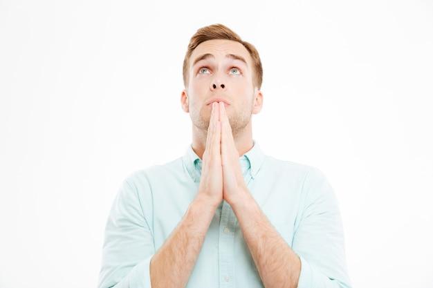 Close de um jovem empresário pacífico orando e olhando para cima