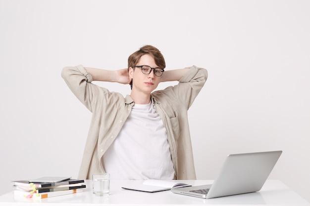Close de um jovem estudante relaxado e confiante usando uma camisa bege e óculos, sentado com as mãos na cabeça à mesa com o computador laptop e notebooks isolados sobre a parede branca