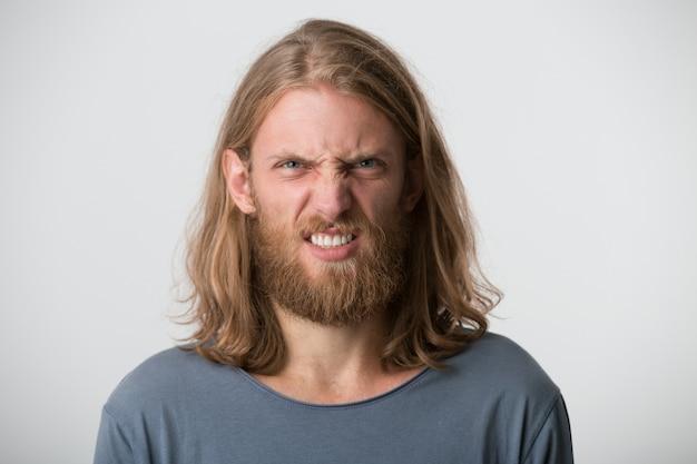 Close de um jovem louco louco com barba e cabelo comprido loiro usa uma camiseta cinza parece irritado e descontente isolado sobre uma parede branca