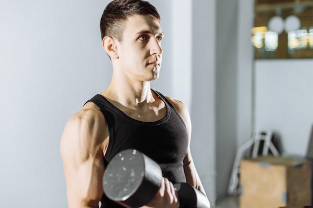 Close de um jovem musculoso levantando pesos no ginásio