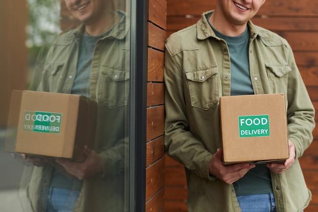 Close de um jovem pedindo comida para entrega e, recebendo, ele está do lado de fora