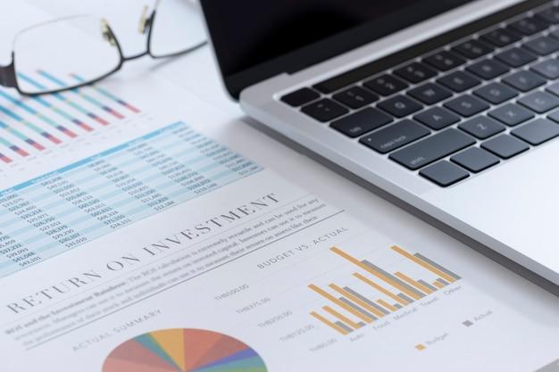 Close de um laptop ou notebook e relatórios financeiros com gráficos coloridos