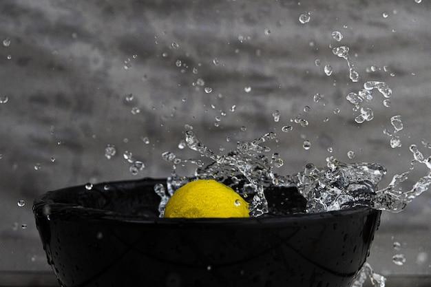 Close de um limão e espirrando água em uma tigela preta sob as luzes contra uma parede cinza