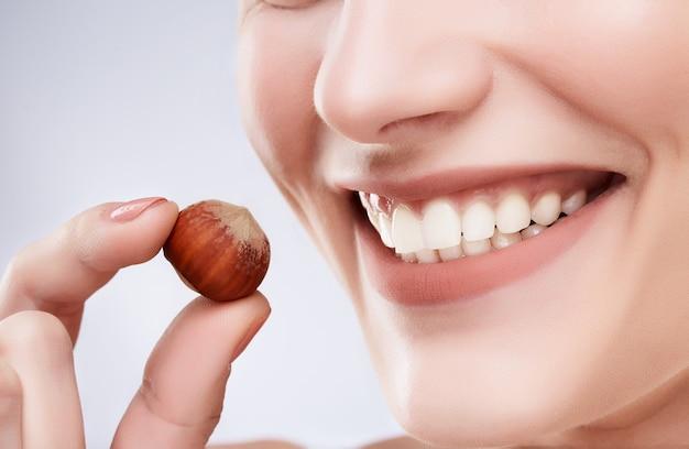 Close de um lindo sorriso branco como a neve. dentes brancos fortes ideais, cuidados com os dentes. cuidados de saúde, conceito estomatológico para dentistas. apenas sorria, segurando avelã perto da boca