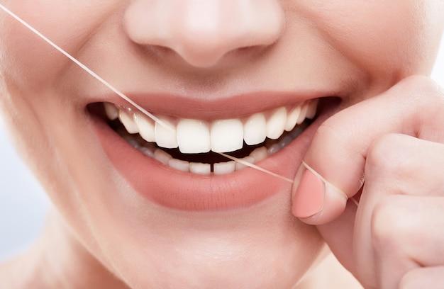 Close de um lindo sorriso branco como a neve. dentes fortes e brancos, cuidados com os dentes. cuidados de saúde, conceito estomatológico para dentistas. limpeza dos dentes com fio dental