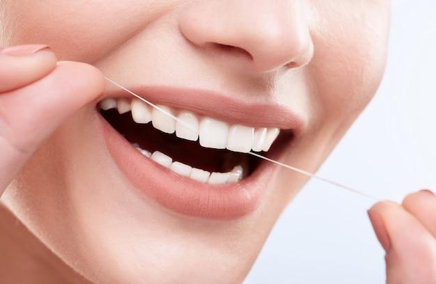 Close de um lindo sorriso branco como a neve. dentes fortes e brancos, cuidados com os dentes. cuidados de saúde, conceito estomatológico para dentistas. só sorria, limpando os dentes com fio dental