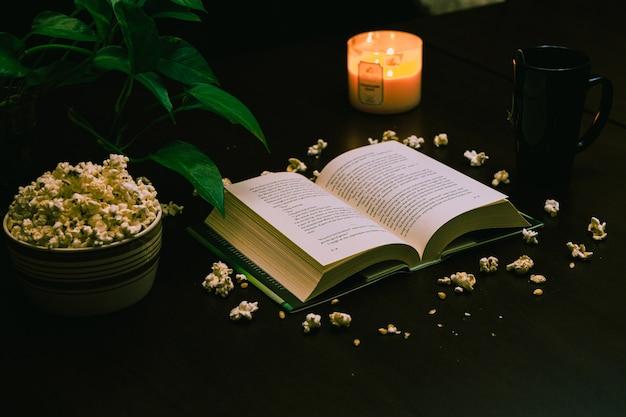 Close de um livro aberto e uma tigela de pipoca na mesa com uma vela acesa e uma xícara de café