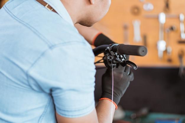 Close de um mecânico usando luvas instalando um cabo de freio de bicicleta