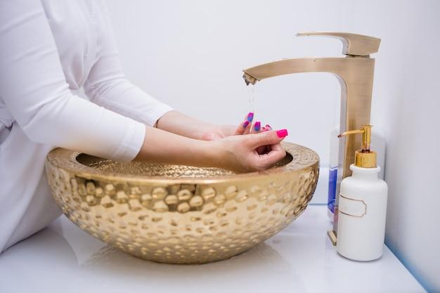Close de um médico de uniforme branco em pé e lavando as mãos na pia do escritório