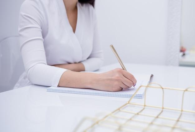 Close de um médico fazendo uma anotação em um caderno