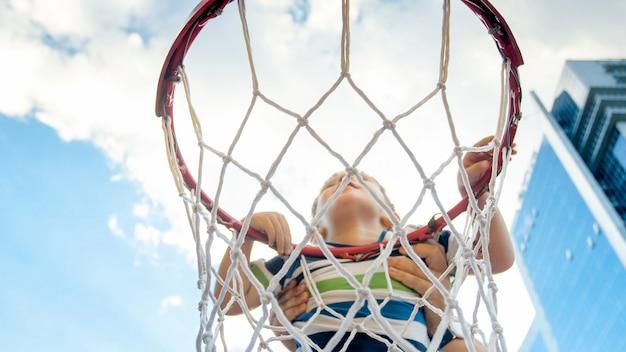 Close de um menino ativo de 3 anos segurando o anel da rede de basquete