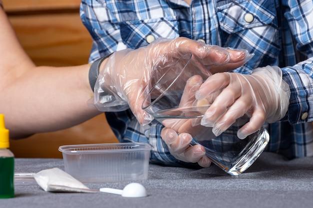 Close de um menino e sua mãe, os cientistas colocam água em um recipiente com elementos químicos