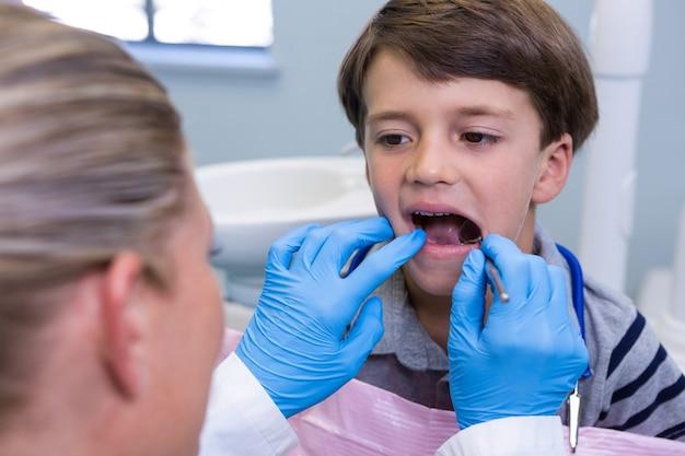 Close de um menino examinando dentista