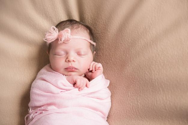 Close de um menino recém-nascido dormindo sobre um cobertor rosa