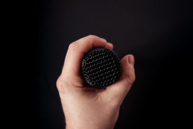 Close de um microfone na mão de uma pessoa no preto