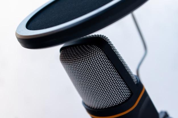Close de um microfone preto e cinza capturado em um fundo branco