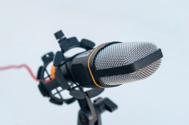 Close de um microfone preto e cinza em uma superfície e fundo brancos