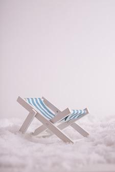 Close de um minúsculo brinquedo com espreguiçadeira na neve