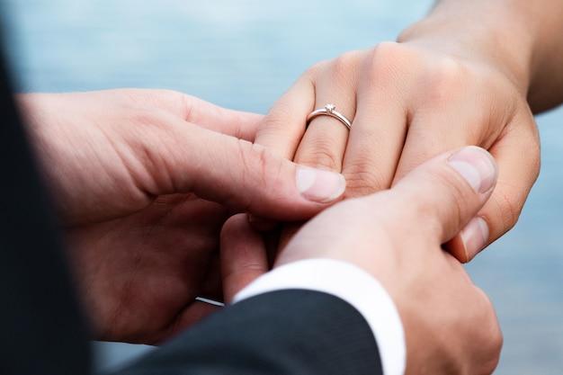 Close de um noivo colocando um anel no dedo da noiva sob as luzes