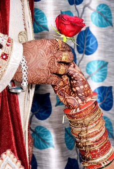 Close de um noivo indiano dando uma rosa para uma noiva durante a cerimônia de casamento