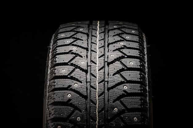 Close de um novo pneu com tachas de inverno em um fundo preto, vista frontal
