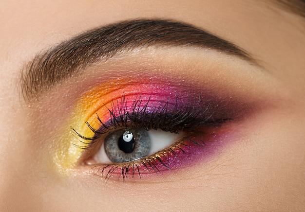 Close de um olho de mulher com uma bela maquiagem colorida