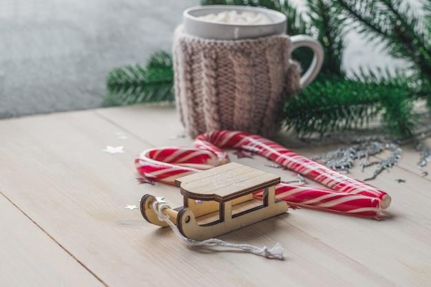 Close de um ornamento de trenó de madeira com bastões de doces e uma caneca de marshmallows na mesa
