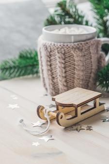 Close de um ornamento de trenó de madeira com uma caneca de marshmallows na mesa de madeira