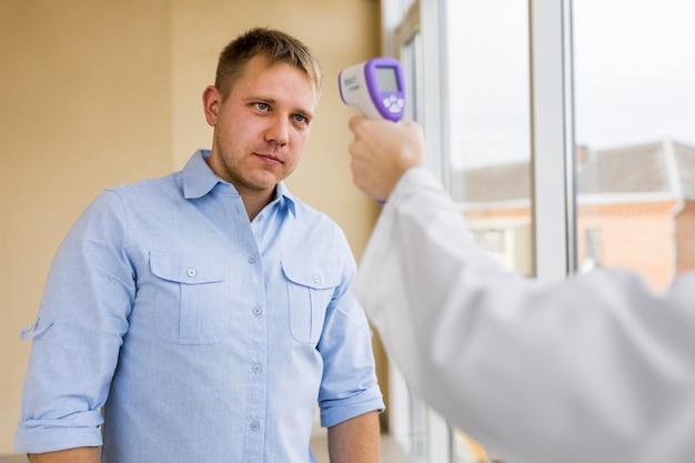 Close de um paciente verificando sua temperatura