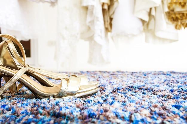 Close de um par de sapatos de noiva na sala de montagem com fundo de vestidos de noiva