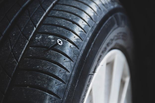 Close de um parafuso de metal afiado perfurando um pneu de carro