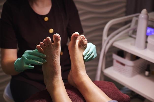 Close de um pedicure massageando suavemente as pernas da mulher após a pedicure