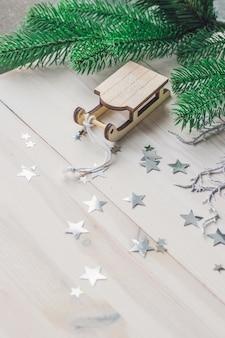 Close de um pequeno enfeite de trenó de madeira na mesa sob as luzes