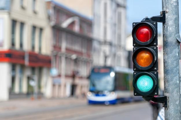 Close de um pequeno semáforo de tráfego com luz verde contra o tráfego da cidade como pano de fundo