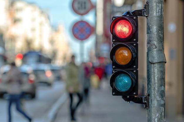 Close de um pequeno semáforo de tráfego com luz vermelha contra o backdro do tráfego da cidade