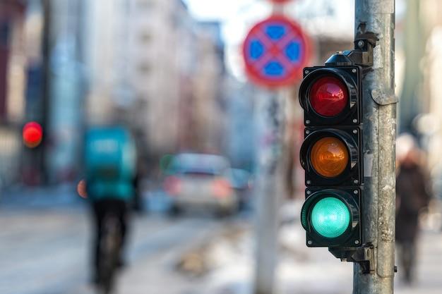 Close de um pequeno semáforo de trânsito com luz verde em contraste com o trânsito da cidade