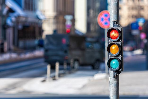 Close de um pequeno semáforo de trânsito com luz vermelha em contraste com o trânsito da cidade