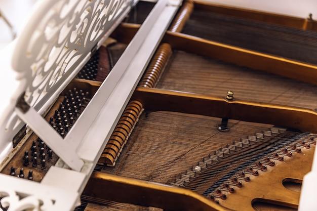 Close de um piano por dentro. instrumento com cordas de metal esticadas horizontalmente.